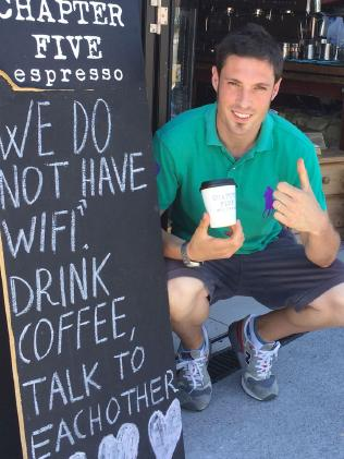 Dom Di Miscio with anti-WiFi sign out of the front of Chapter Five Espresso